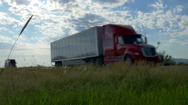 Big freight semi trucks speeding and passing by on highway across the country video