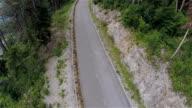 Big group of longboard riders speeding down the road aerial video