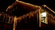 CLOSE UP: Big house decorated with white glowing lights on Christmas evening video