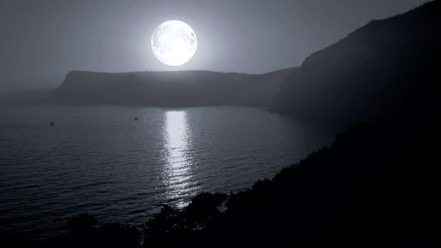 Big moon illuminates the mountains and the sea video