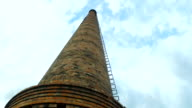 Big old  pipe  of  factory against the sky. The pipe is made of red brick. video
