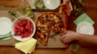 Big pizza on table for three people, man take one piece of warm snack video