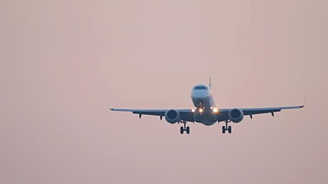 Big plane landing at sunset sky, flying airplane on red sunrise sky video