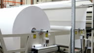 Big roll of paper turning on spindle in manufacturing video