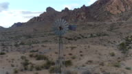 AERIAL: Big vintage windmill under beautiful rocky mountains video