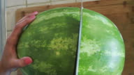 A big Watermelon being cut by a big knife video