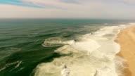 Big waves on sandy beach of the western coast of Portugal aerial video