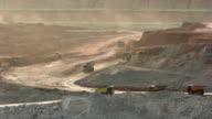 big yellow mining trucks at work in coal mine. video