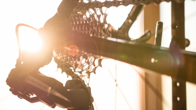 Bike frame detail, wheel spoke, gear and chain at sunset video