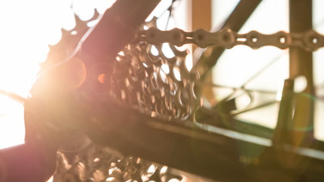 Bike wheel, gear and chain in motion, illuminated by sunlight video