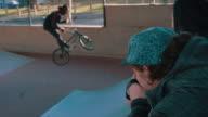 BMX biker driving through stunt park video
