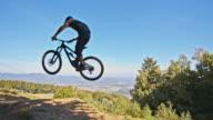 SLO MO MTB biker jumping on a downhill trail video