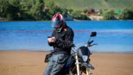 Biker on the bank of the river, next to his bike, he is looking for the phone video