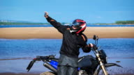 Biker on the bank of the river, next to his motorcycle, makes the photo on the phone video