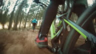 POV Biker pedaling down forest trail with friends video