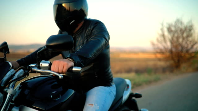 Biker riding motorcycle on an empty road at sunset video