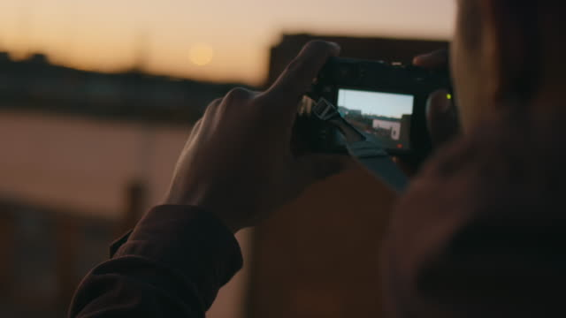 BMX biker taking pictures on rooftop video