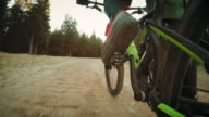 POV of a biker's leg pedaling on forest road video