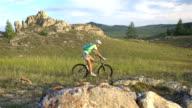 biking woman cycling on green meadow video