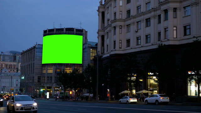 A Bilboard with a green screen on a busy street. video