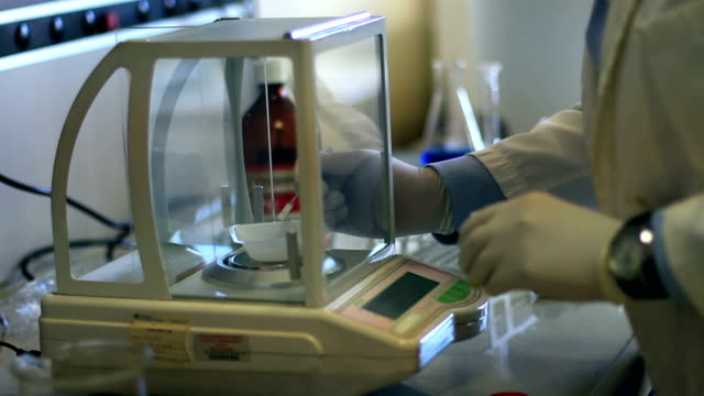bio chemist weighing chemical compound video
