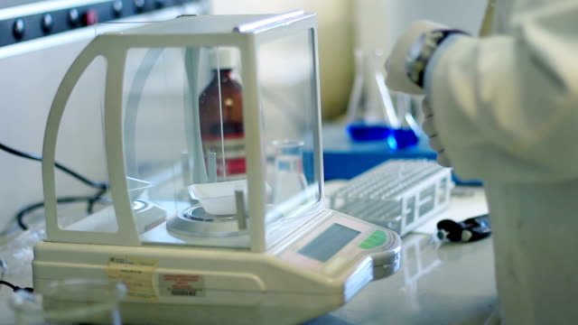 biochemist weighing chemical compound video