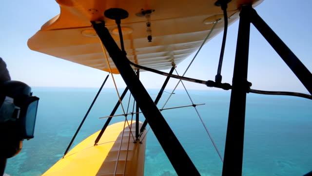 Biplane over ocean. video