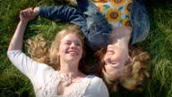 Bird's Eye View Of Two Sisters Laying In A Field, Holding Hands, And Having A Conversation video