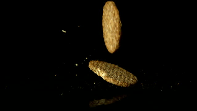 Biscuits falling on black surface video