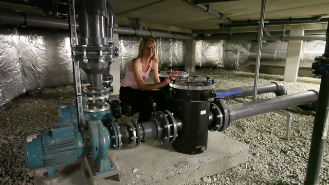 Bizarre engineer thinking happily while relaxing among water pumps video