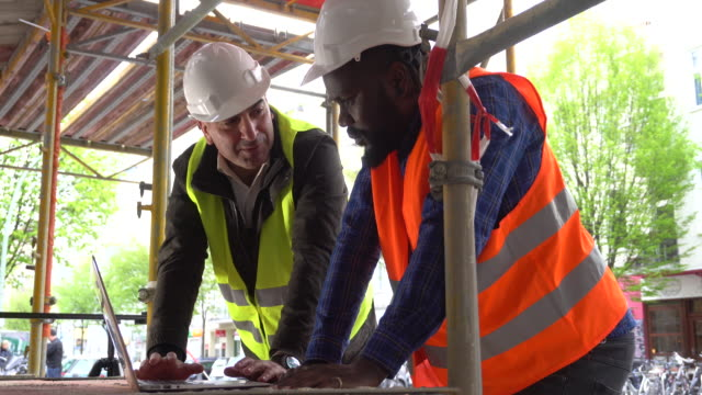 A black and a white engineers looking at the computer among scaffolding video