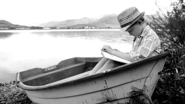 Black and white footage: a boy sits in a wooden boat and reads a book video