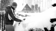 Black and white footage: Man cleaning car after snow blizzard video