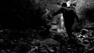 Black and white footage: mother and son climbing their way up to the waterfall in the twilight video