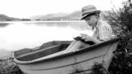 Black and white footage of a boy sitting in a boat at the lake and reads video