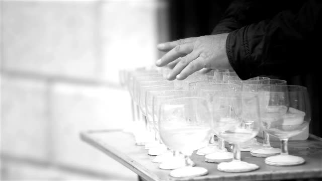 Black and white footage of a busker playing the wine glasses video
