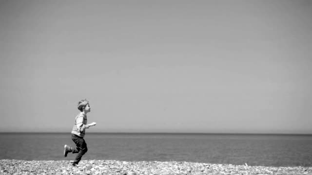 A black and white footage of a kid running along the seacoast video