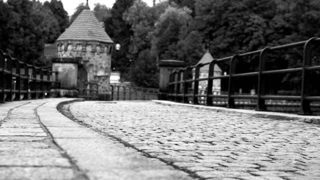 Black and white footage of a man walking by the cobbled dam video