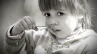 Black and White portrait : Cute Little girl eats with spoon video