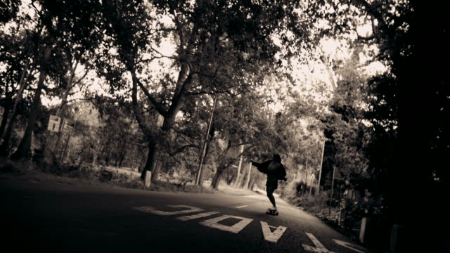 Black and white Skater girl in leather jacket riding along road with trees video