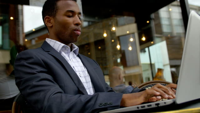 black businessman working with laptop in a cafe: cafeteria, outdoor video