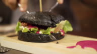 Black charcoal burger with red sauce being cut. New trend healthy black food video