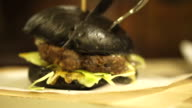 Black charcoal lamb burger with honey mustard sauce and lettuce. New fusion trend healthy black food video