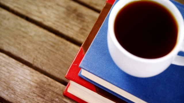 Black coffee on book stack 4k video