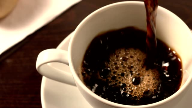 Black coffee pouring into cup with saucer video