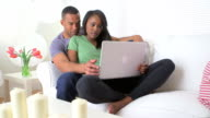 Black couple browsing the internet on laptop video