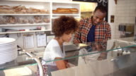 Black couple working behind the counter at a sandwich bar video