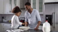 Black dad and his young daughter baking together at home, shot on R3D video
