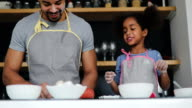 Black dad and young daughter baking together in the kitchen video