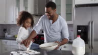 Black dad and young daughter prepare cakes for baking, shot on R3D video